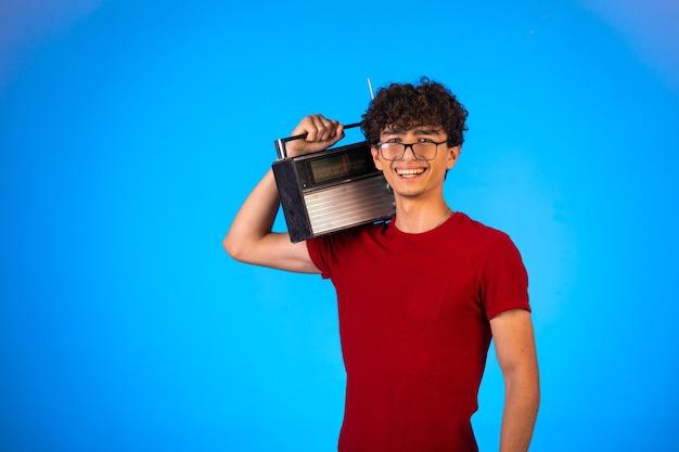 Kręcone włosy chłopiec w czerwonej koszuli, trzymając vintage radio i uśmiechnięty.