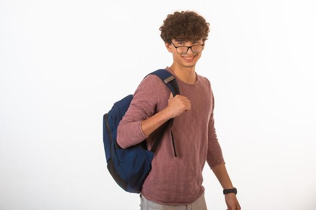 Kręcone włosy chłopiec w okularach optique, trzymając plecak i uśmiechnięty.