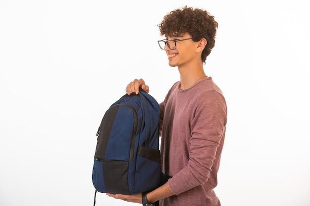 Kręcone włosy chłopiec w okularach optique, trzymając plecak, patrząc na bok i uśmiechnięty.