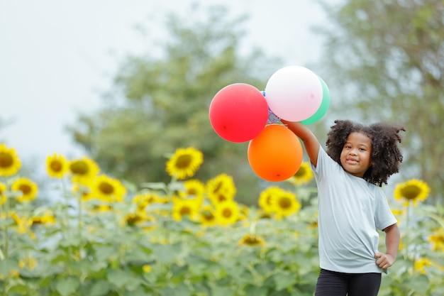 Kręcone włosy dziewczyna szczęśliwie łapie kolorowe balony na polu słonecznika na wakacjach