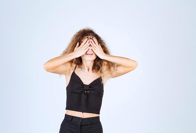 Kręcone włosy dziewczyna zamykając część twarzy ręką.