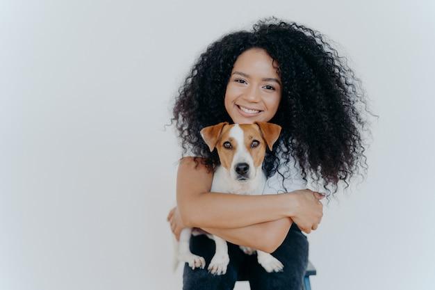 Kręcone włosy kobieta obejmuje ulubionego psa, uśmiecha się przyjemnie, stoi na białym tle