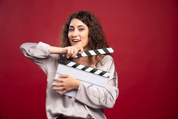 Kręcone włosy kobieta trzyma clapperboard.