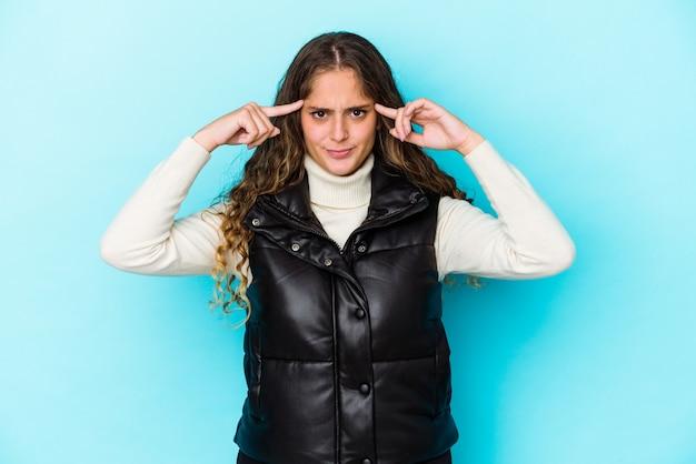 Kręcone włosy kobieta trzyma palce wskazujące skierowane w głowę