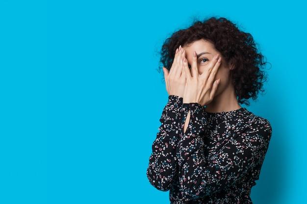 Kręcone włosy kobieta zakrywa twarz dłońmi i uśmiecha się do kamery, pozując na niebieskiej ścianie z wolną przestrzenią