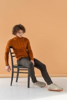 Kręcone włosy mężczyzna w brązowej bluzce pozowanie na krześle