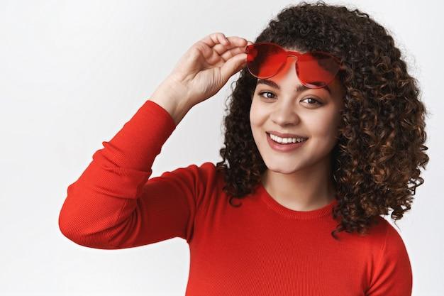 Kręcone włosy stylowa urocza dziewczyna zdejmuje czerwone okulary przeciwsłoneczne spojrzenie spotykasz przyjaciela słoneczny spacer park stoi biała ściana uśmiechnięta zachwycona ciesz się chłodnymi wakacjami, wyglądaj na szczęśliwą beztroską