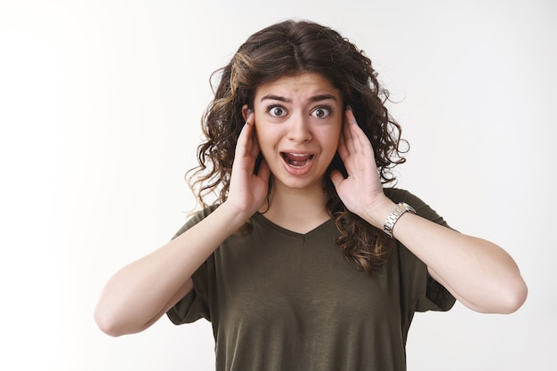 Kręconowłosa ormiańska dziewczyna rozproszona zaniepokojona okropny nieznośny głośny hałas zakrywający uszy krzyczy z prośbą o ściszenie głośności, zaniepokojenie stojąc nie może pracować zatłoczone miejsce, białe tło