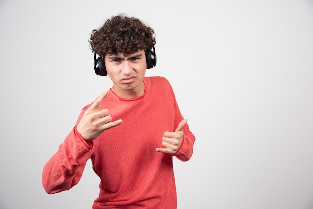 Kręcony młody człowiek ze słuchawkami robi znaki.