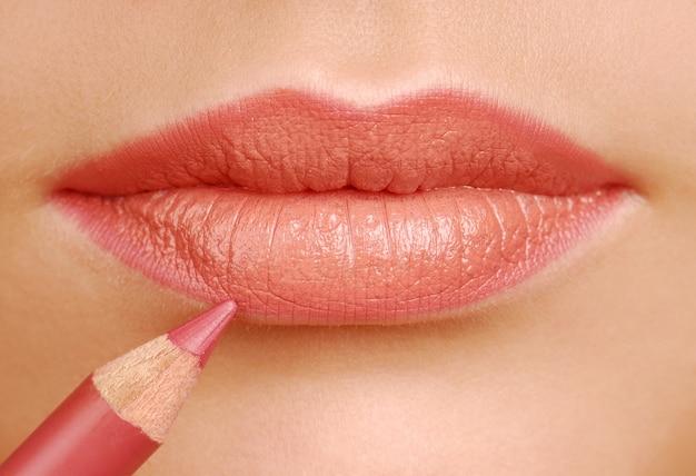 Kredka kosmetyczna czerwona szminka. narzędzie do makijażu. usta kobiety z bliska