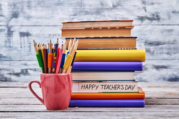 Kredki i stos książek. ciesz się dniem nauczyciela.