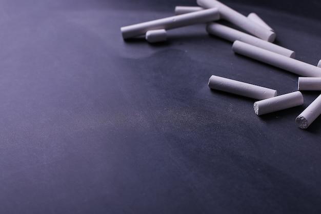 Kredki leżą na czarnej tablicy