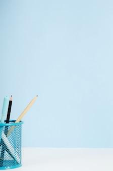 Kredki niebieskie, białe i czarne, długopisy w stojaku na białym stole na niebieskim tle, biurko. skopiuj miejsce.