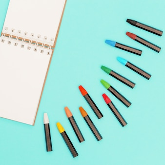 Kredki olejne pastelowe i otwarty notatnik na wiosnę na szkice. miejsce pracy artysty. ogólnospołeczni środki i twórczości tło z kopii przestrzenią.