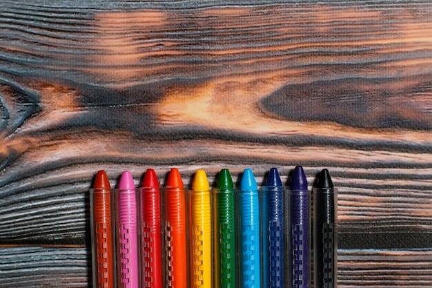 Kredki woskowe o różnych kolorach na rustykalnym drewnianym tle