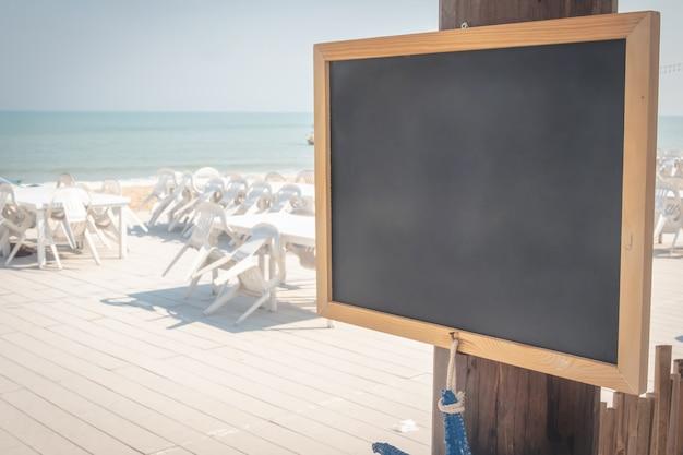 Kredowa deska z drewnianą ramą z piaska plaży tłem