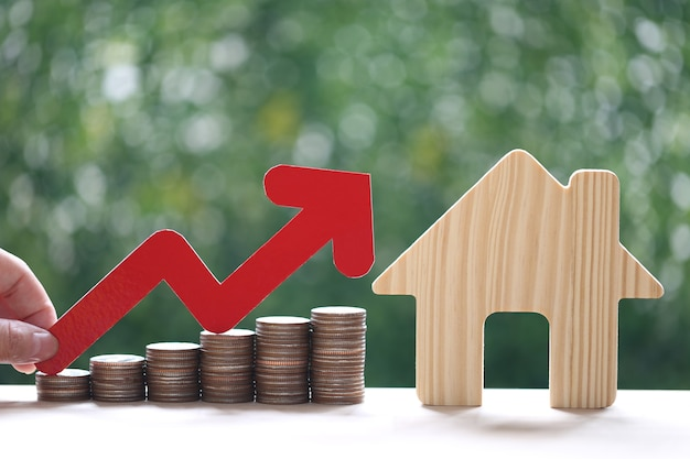 Kredyt hipoteczny, kobieta ręka trzyma wykres z czerwoną strzałką i stos monet pieniędzy z modelowym domem na naturalnym zielonym tle, inwestycje biznesowe i koncepcja nieruchomości
