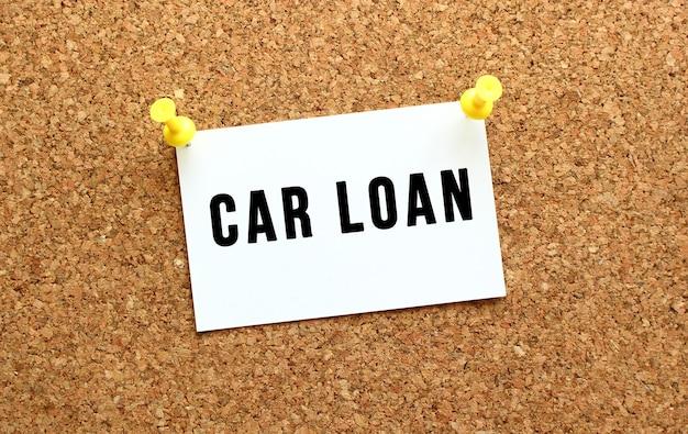 Kredyt samochodowy jest napisany na karcie przyczepionej do tablicy korkowej za pomocą guzika. przypomnienie na tablicy biurowej. pomysł na biznes.