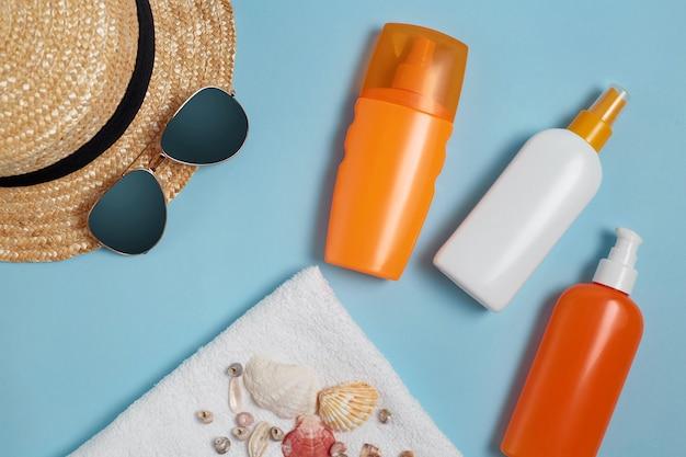 Krem do opalania, kapelusz przeciwsłoneczny, krem, butelka z filtrem przeciwsłonecznym, krem do opalania, butelka balsamu, muszle na niebieskim tle. ochrona przed słońcem.