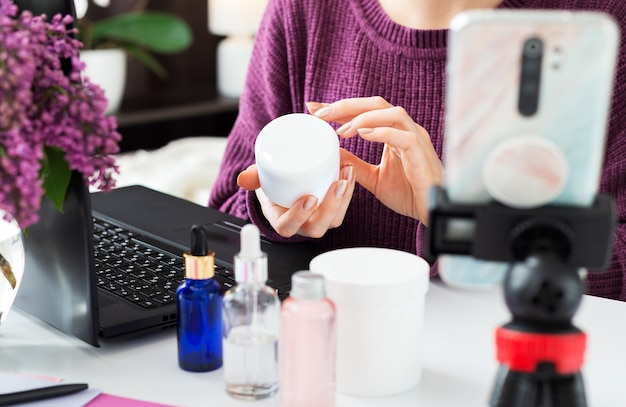 Krem do pielęgnacji ciała. krem w kobiecych rękach blogera piękności. influencer umożliwia nagrywanie treści wideo online, przegląd transmisji na żywo na produktach kosmetycznych. szkolenie kosmetologiczne, poradnik pielęgnacji skóry.