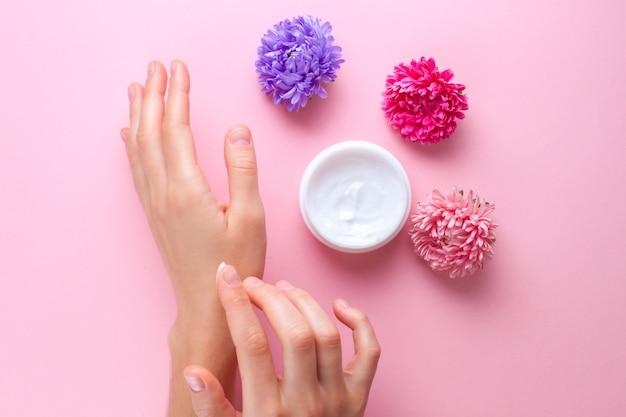 Krem do rąk i kwiaty. pielęgnacja skóry i dłoni. nawilżający i eliminujący suchość skóry dłoni