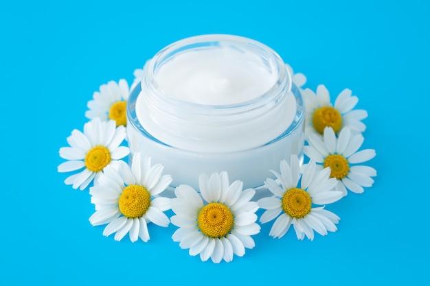 Krem do twarzy w butelce, koncepcja pielęgnacji skóry. kwiat rumianku i szklany słoik