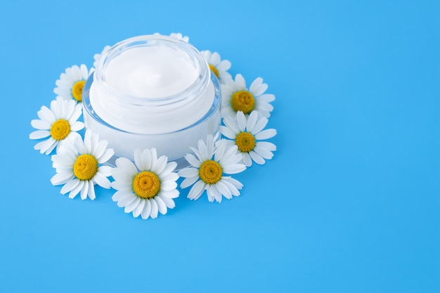 Krem do twarzy w szklanym słoju. kwiaty rumianku i krem nawilżający, balsam