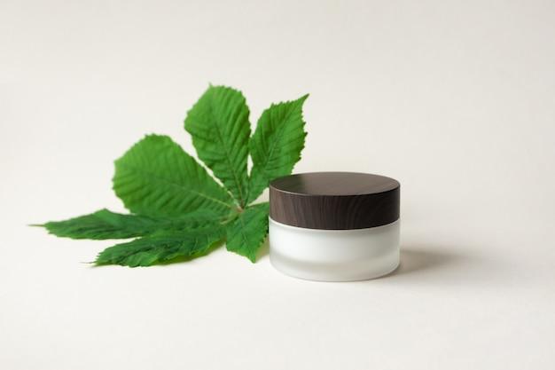 Krem nawilżający lub balsam do ciała w słoiku z matowego szkła z drewnianym kubkiem i liściem kasztanowca na beżowym stole