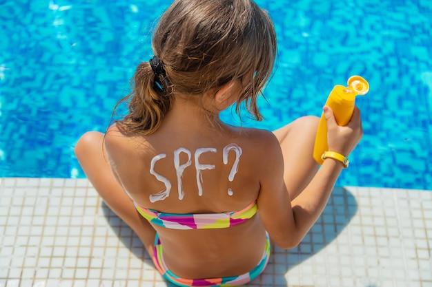 Krem przeciwsłoneczny na plecach dziecka. selektywne skupienie. dziecko.