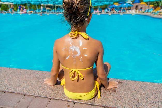 Krem przeciwsłoneczny na plecach dziecka. selektywne skupienie.