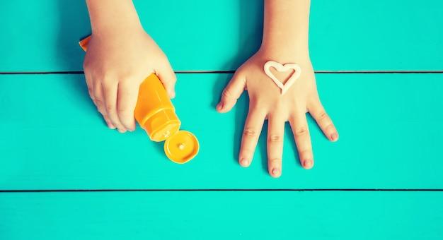 Krem przeciwsłoneczny na ręce dziecka.