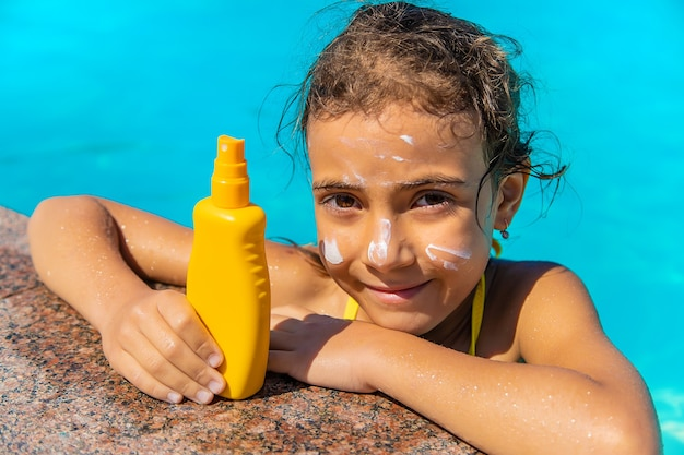 Krem przeciwsłoneczny przy basenie na twarzy dziecka. selektywne skupienie.