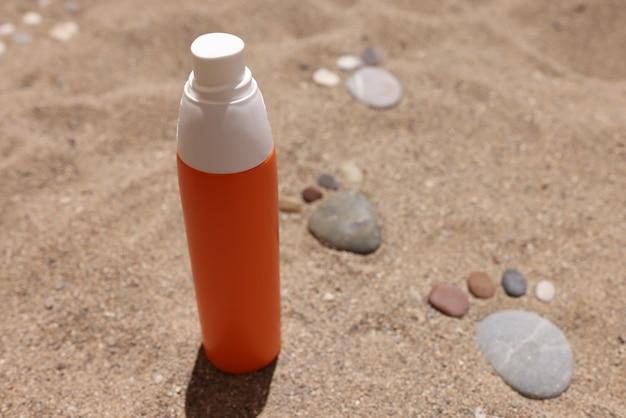 Krem przeciwsłoneczny stoi na piasku obok odlewanych kamieni wyłożonych stopami