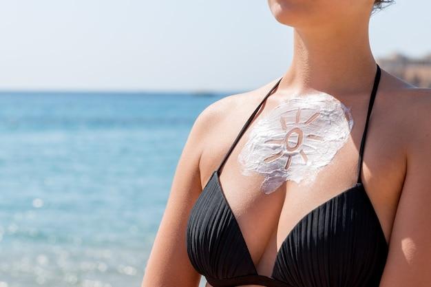 Krem przeciwsłoneczny w kształcie słońca na piersi kobiety na tle morza.