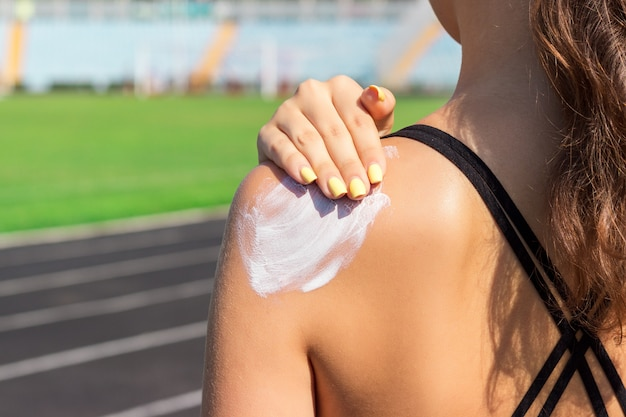 Krem przeciwsłoneczny z filtrem przeciwsłonecznym. kobieta w sportswear kładzenia słonecznej śmietance na ramieniu na pięknym letnim dniu.