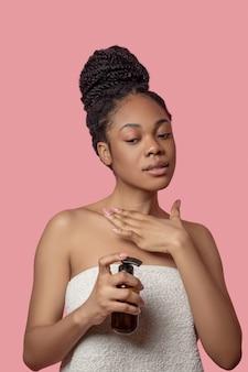 Krem spf. ciemnoskóra kobieta nakłada krem nawilżający na ciało przed opalaniem