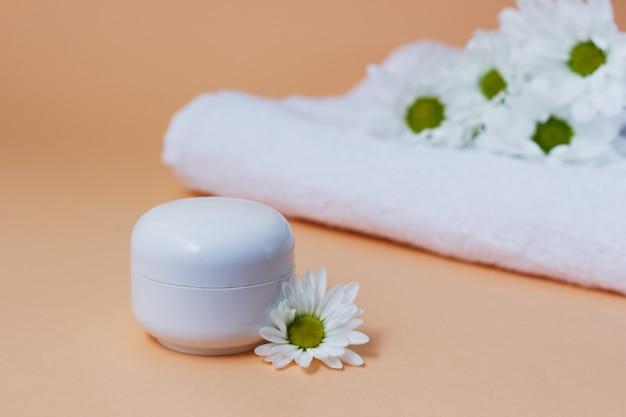 Krem w białej tubce lub butelce na beżowym tle z kwiatami białej chryzantemy produkt kosmetyczny do pielęgnacji skóry