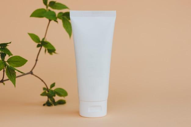 Krem w białej tubie z naturalnymi liśćmi