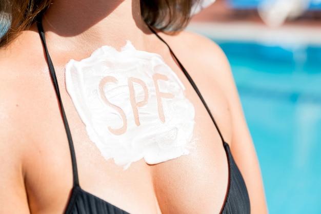 Krem z filtrem przeciwsłonecznym jako słowo spf na kobiecej piersi przy basenie. koncepcja współczynnika ochrony przed słońcem. współczynnik ochrony przeciwsłonecznej na wakacjach, koncepcja.