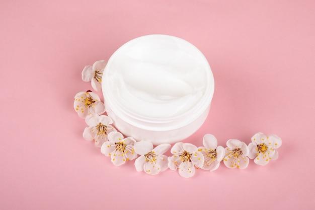 Krem z kwiatami na różowym tle, uroda pielęgnacji skóry.