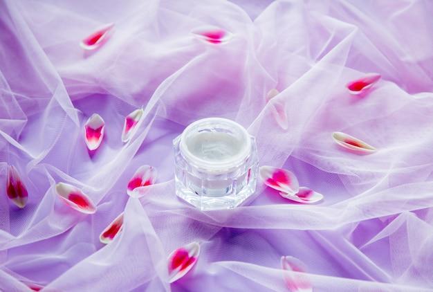 Krem z płatkami tulipanów na fioletowym tiulu. naturalne światło