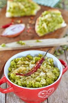 Krem z zielonego groszku z sosem olejkowym i cebulą w małym garnku i rozłóż na kromkach chleba.