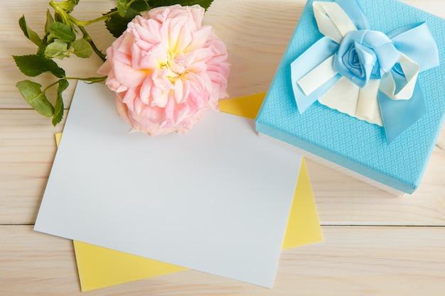 Kremowa róża i pocztówka na napis motywacyjny lub powitalny.