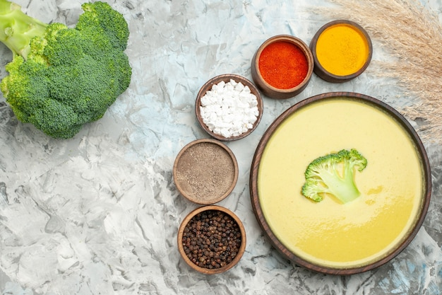 Kremowa zupa brokułowa w brązowej misce różne przyprawy i świeże brokuły na szarym stole