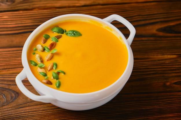 Kremowa zupa dyniowa w misce z nasionami i bazylią na drewnianym tle. święto dziękczynienia, jesienna zupa