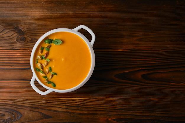 Kremowa zupa dyniowa w misce z pestkami i bazylią