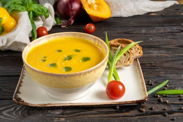 Kremowa zupa dyniowa z sosem pesto, cebulą i pomidorkami koktajlowymi.