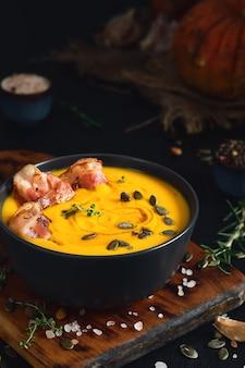 Kremowa zupa dyniowa ze smażonymi plastrami boczku ze śmietaną i pestkami dyni w czarnej misce na czarnym drewnianym stole. zbliżenie, selektywna ostrość. składniki do przygotowania sezonowej zupy dyniowej na stole