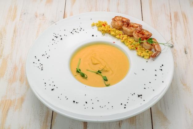 Kremowa zupa olejowo-przyprawowa podawana z krewetkami