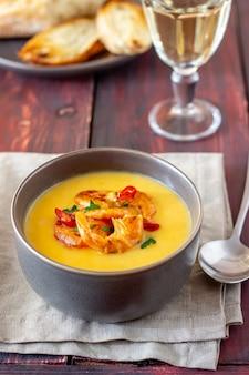 Kremowa zupa serowa z grillowanymi krewetkami na drewnianym tle.